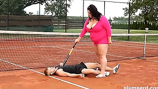 Obese woman facesits on her trainer at the tennis locality